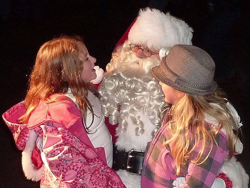 Santa talks to 2 little girls.